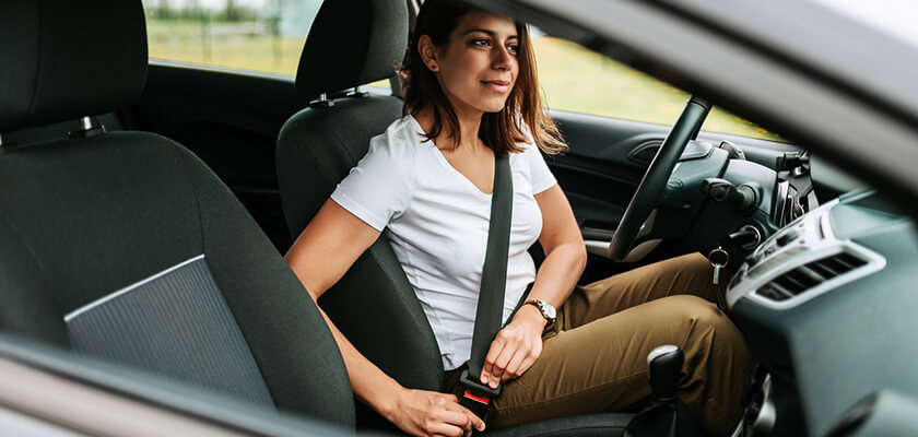 Woman in car putting on her seat belt